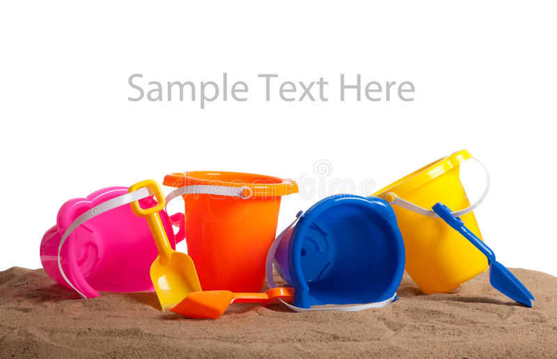 Assorted colored buckets on sand with copy space stock photos