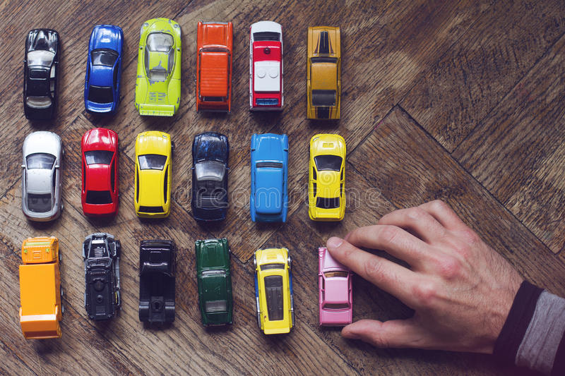 Assorted colorful car collection on floor. Horizontal top view of male hand arranging an assorted metal colorful toy car collection on brown wooden floor in royalty free stock photography