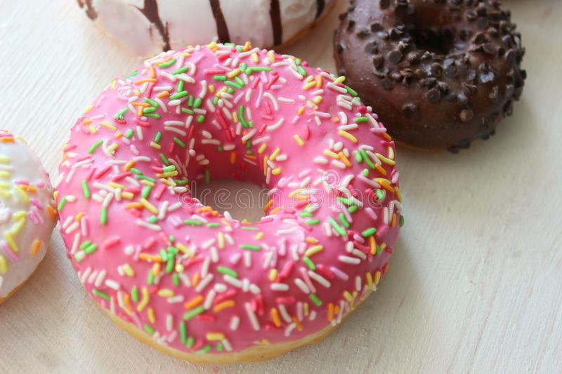 Assorted colorful donuts close-up. Photos of different donuts. Assorted colorful donuts in pink, green, chocolate icing close-up, sweet dessert stock photos