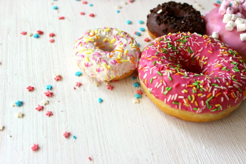 Assorted colorful donuts close-up. Photos of different donuts. Assorted colorful donuts in pink, green, chocolate icing close-up, sweet dessert stock photo