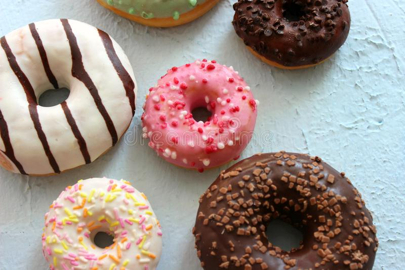 Assorted colorful donuts close-up. Photos of different donuts. Assorted colorful donuts in pink, green, chocolate icing close-up, sweet dessert.n stock photography