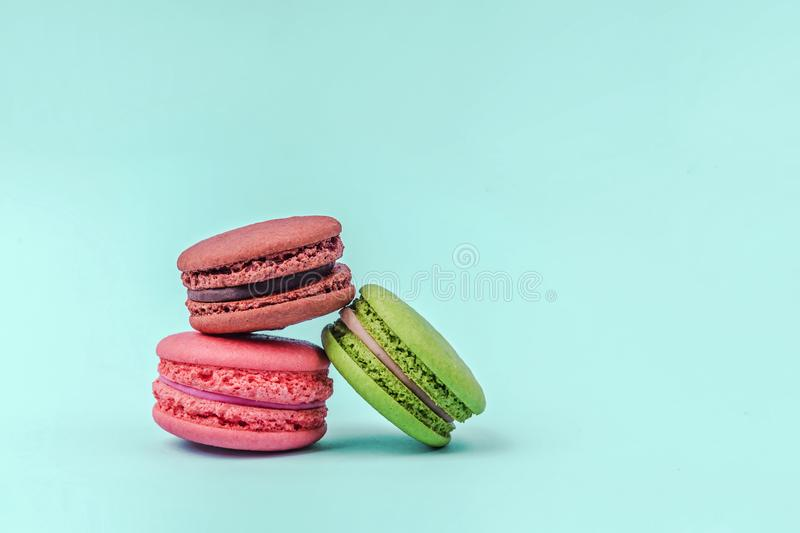 Assorted colorful macaroons on mint green background with copy space. stock photo