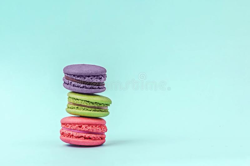 Assorted colorful macaroons on mint green background with copy space. stock image