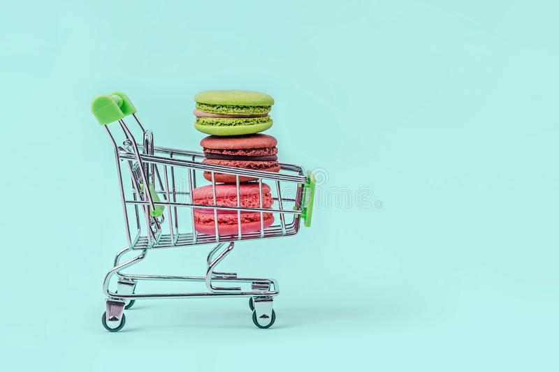 Assorted colorful macaroons in toy shopping cart on mint green background with copy space. royalty free stock image