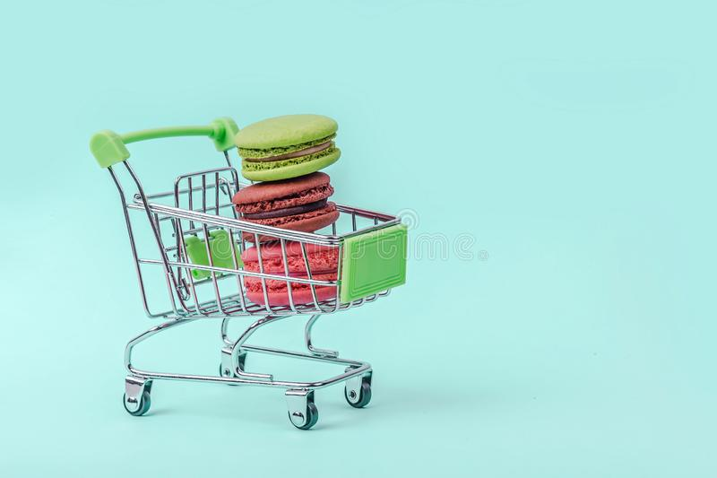 Assorted colorful macaroons in toy shopping cart on mint green background with copy space. royalty free stock photo