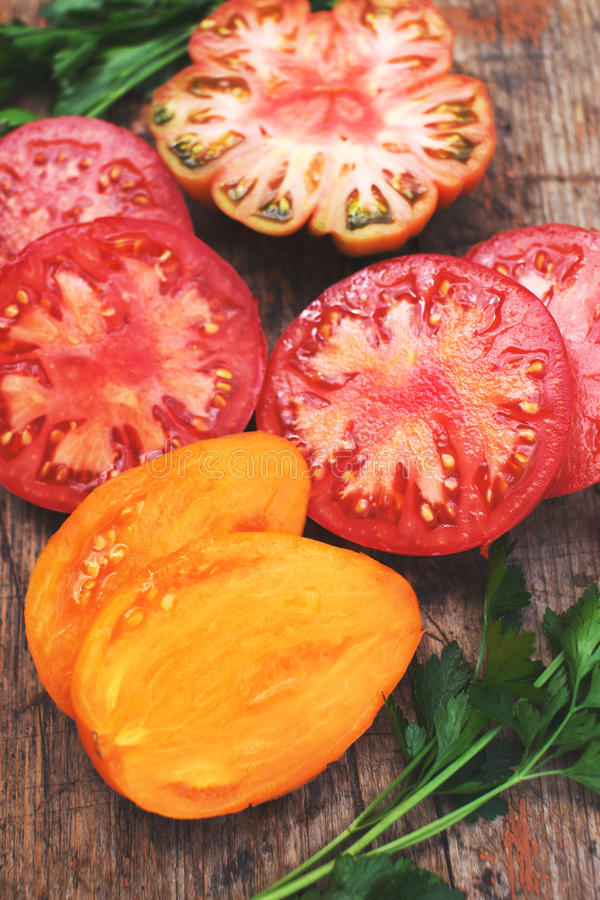 Assorted Colorful Sliced Heirloom Tomatoes. On rustic wood background royalty free stock images