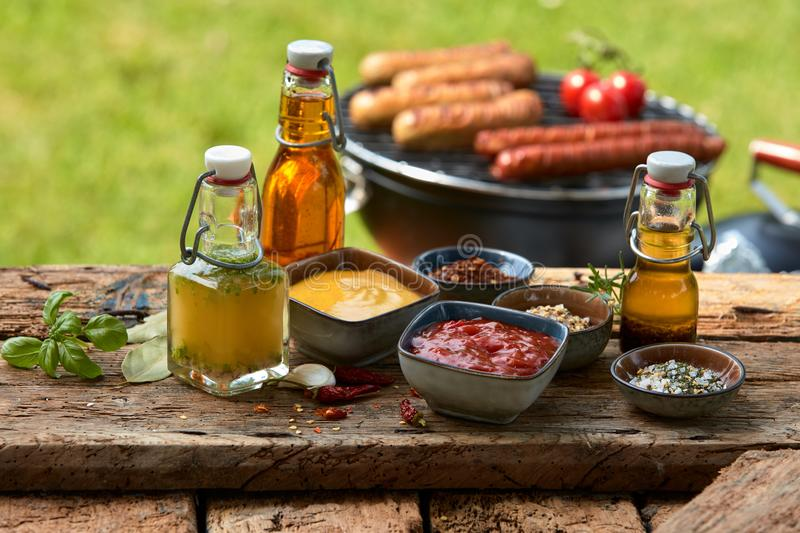 Assorted condiments and spices on a picnic table. Assorted condiments and spices for a summer barbecue on a rustic wood picnic table outdoors in the garden with stock photo