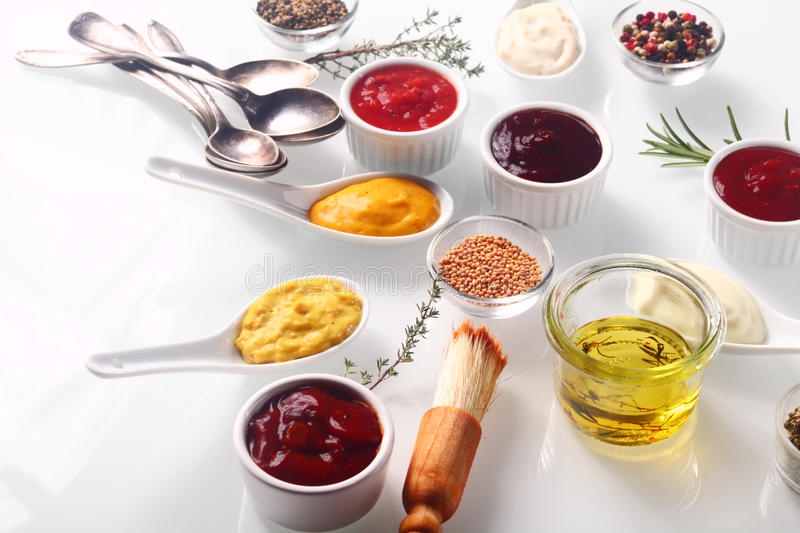 Assorted Condiments on White Wooden Table. Close up Assorted Fresh Condiments on White background with Herbs stock photos