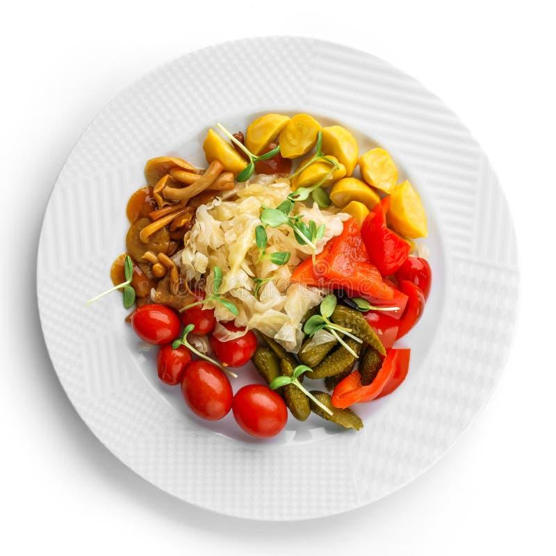 Assorted conservó en vinagre las verduras con la col de la chucrut, pimientas, pepinos, tomates, setas en la placa aislada en el  imágenes de archivo libres de regalías
