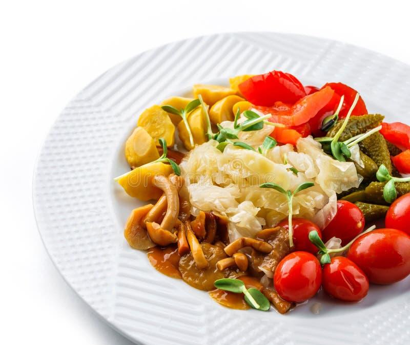 Assorted conservó en vinagre las verduras con la col de la chucrut, pimientas, pepinos, tomates, setas en la placa aislada en el  foto de archivo