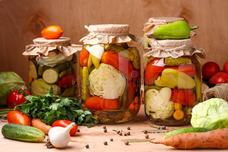 Assorted conservó en vinagre verduras en tarros: pepinos, tomates, col, calabacín y pimientas con las hojas del ajo, del eneldo y imagenes de archivo