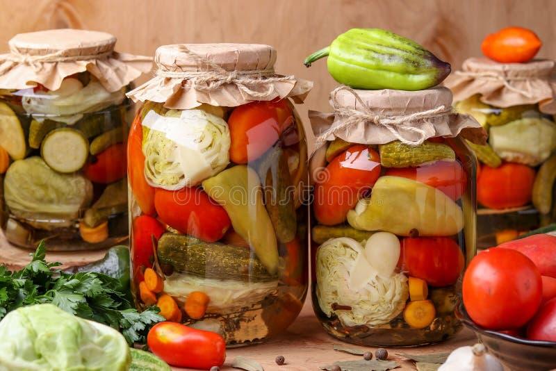 Assorted conservó en vinagre verduras en tarros: pepinos, tomates, col, calabacín y pimientas con las hojas del ajo, del eneldo y fotografía de archivo libre de regalías