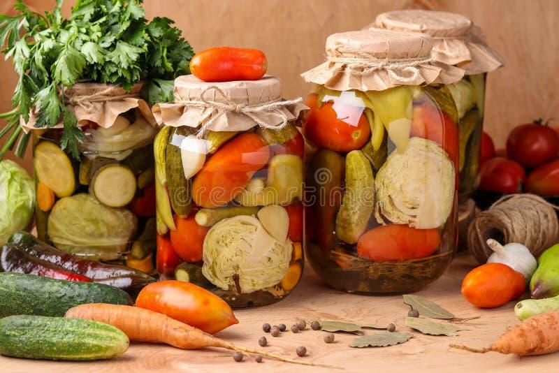 Assorted conservó en vinagre verduras en tarros: pepinos, tomates, col, calabacín y pimientas con las hojas del ajo, del eneldo y imagen de archivo libre de regalías