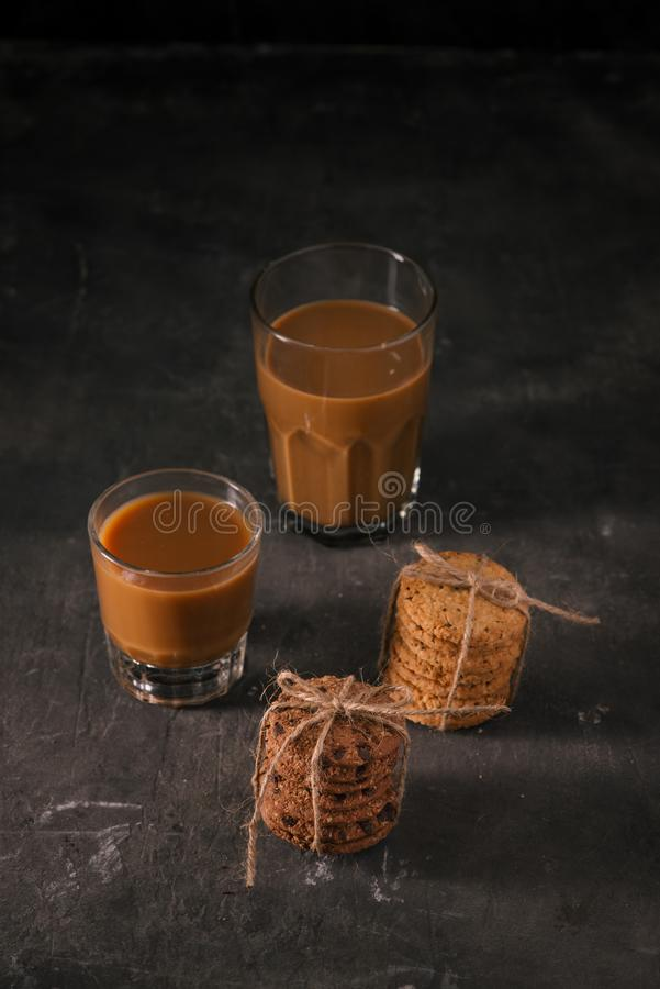 Assorted cookies in brown paper and glass of coffee with milk on. Dark background stock photos
