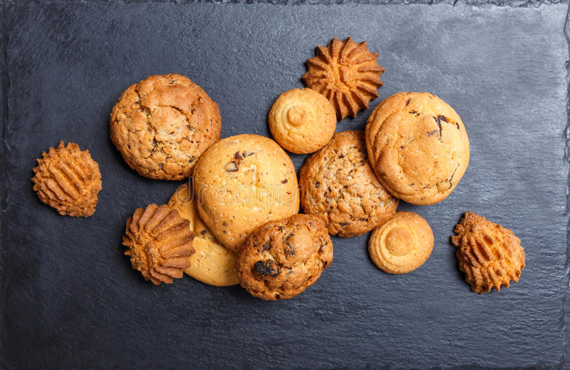 Assorted cookies with chocolate chip, oatmeal raisin on stone slate background on wooden background close up. Homemade baking royalty free stock photos