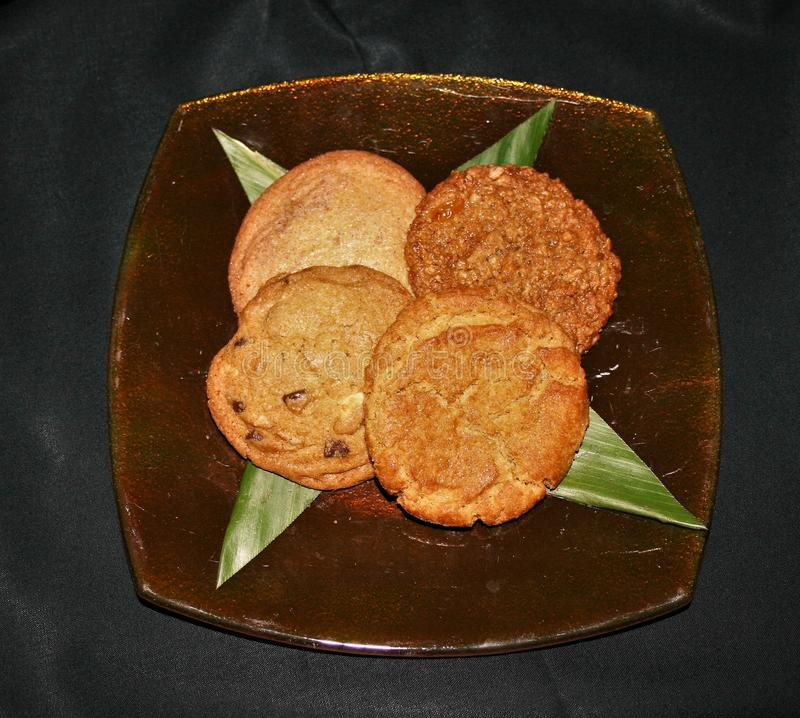 Assorted cookies on a glass plate with a black background royalty free stock photography