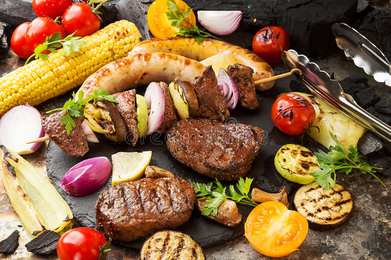 Assorted delicious grilled barbecue meat with vegetable. Beef gr. Illed steaks with spicy sausages, beef kebabs, corn, cherry tomato, pepper, slices of onion royalty free stock image