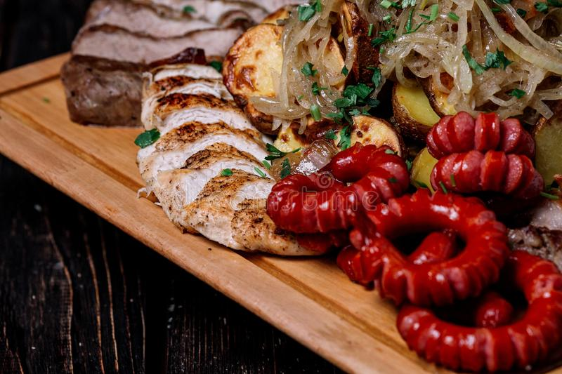 Assorted delicious grilled meat, sausages and vegetables on cutt royalty free stock photography