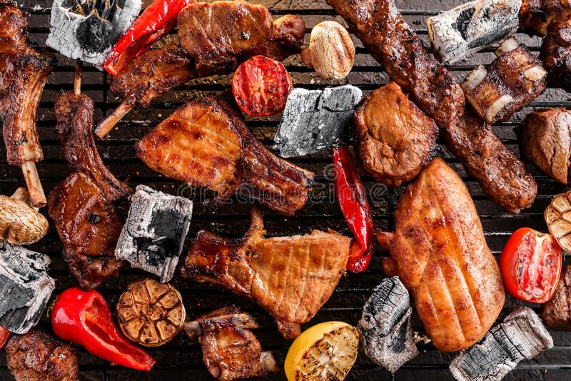 Assorted delicious grilled meat with vegetables over the coals on a barbecue, dark background with light of fire. Top view.  royalty free stock photography
