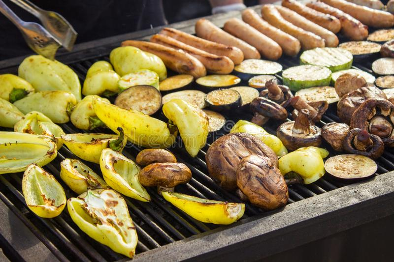 Assorted delicious grilled meats with vegetables over the barbecue on the charcoal. Sausages, steak, pepper, mushrooms, zucchini stock photo