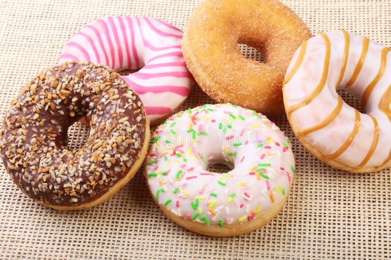 Assorted delicious homemade doughnuts in the glaze, colorful sprinkles and nuts . stock images
