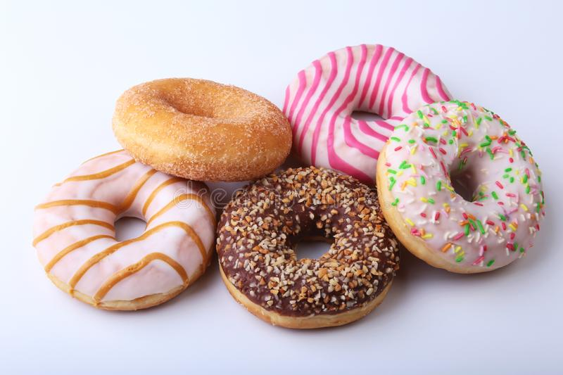 Assorted delicious homemade doughnuts in the glaze, colorful sprinkles and nuts isolated on white background. royalty free stock image