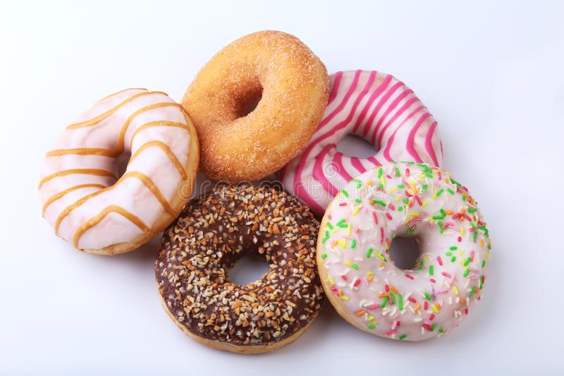Assorted delicious homemade doughnuts in the glaze, colorful sprinkles and nuts isolated on white background. royalty free stock photography
