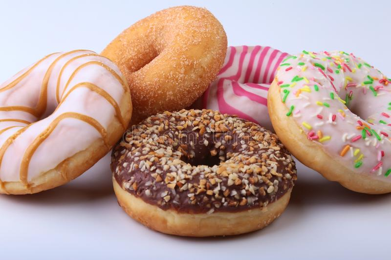 Assorted delicious homemade doughnuts in the glaze, colorful sprinkles and nuts isolated on white background. royalty free stock photos