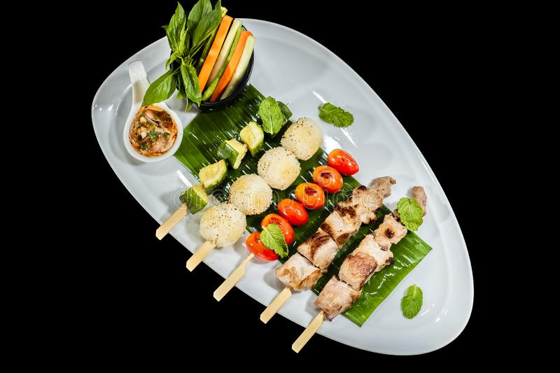 Assorted delicious mixed grilled with vegetable on white plate on black background stock photos