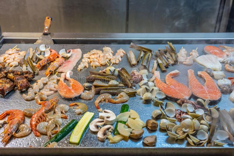 Assorted delicious seafoods grilled on big square pan in buffet stock photo
