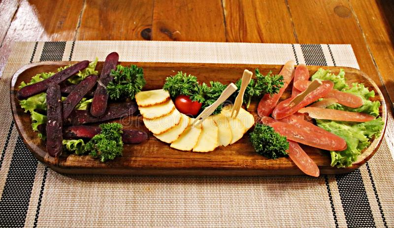 Assorted different varieties of dried sausage, smoked cheese, vegetables and lettuce on a large wooden plate stock image