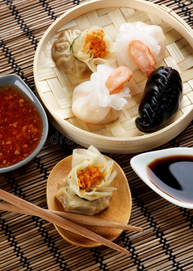 Assorted Dim Sum. In Bamboo Steamed Bowl and Tori with Chiken on Wooden Plate with Red Chili and Soy Sauces and Chopsticks closeup on Straw Mat background stock photography