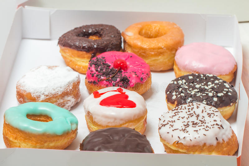 Assorted donuts in a box. Picture of assorted donuts in a box with chocolate frosted, pink glazed and sprinkles donuts royalty free stock images