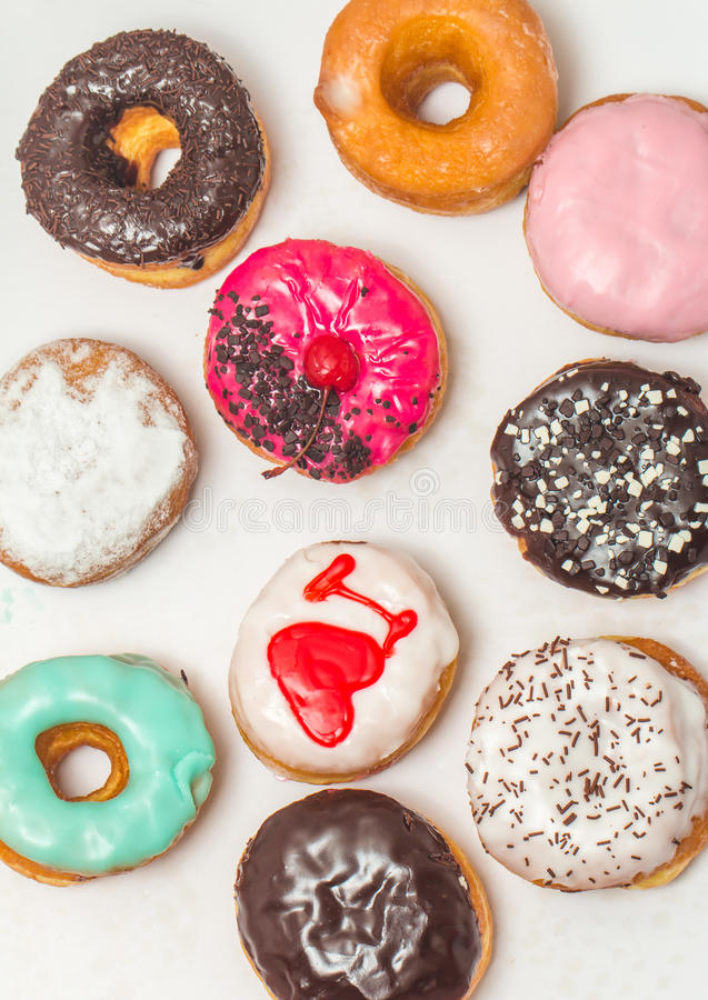 Assorted donuts in a box. Picture of assorted donuts in a box with chocolate frosted, pink glazed and sprinkles donuts. Top view stock photos