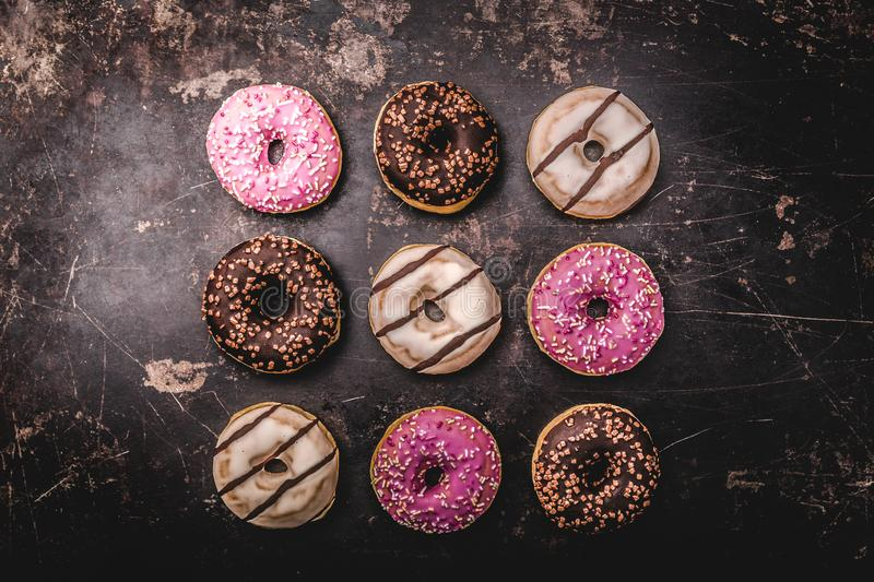 Assorted donuts with chocolate. On dark background royalty free stock image