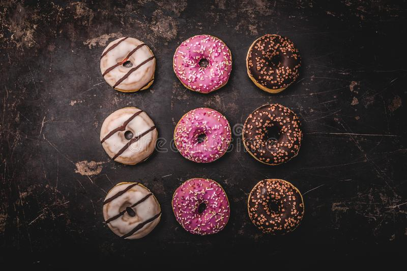 Assorted donuts with chocolate. On dark background royalty free stock images