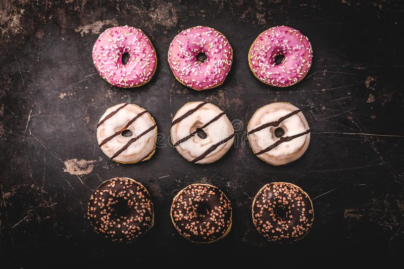 Assorted donuts with chocolate. On dark background stock image