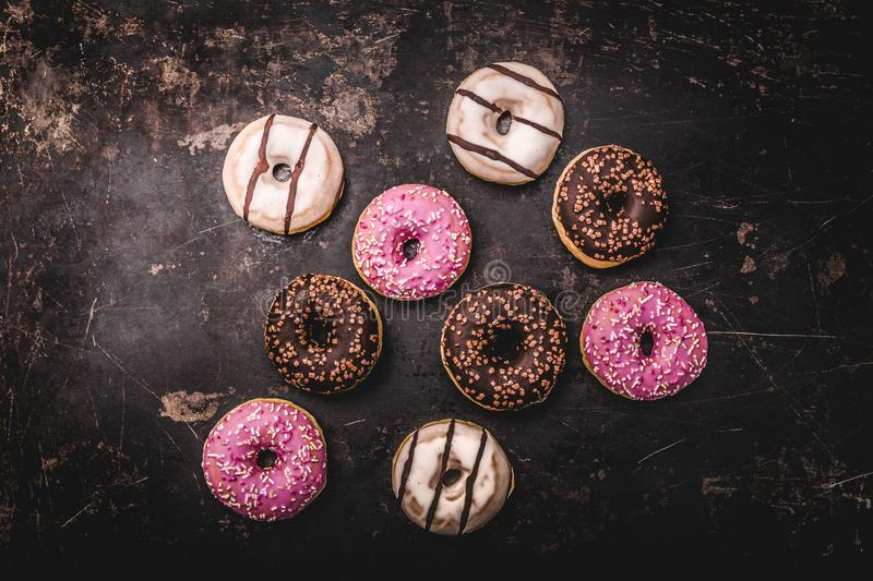 Assorted donuts with chocolate. On dark background stock photography