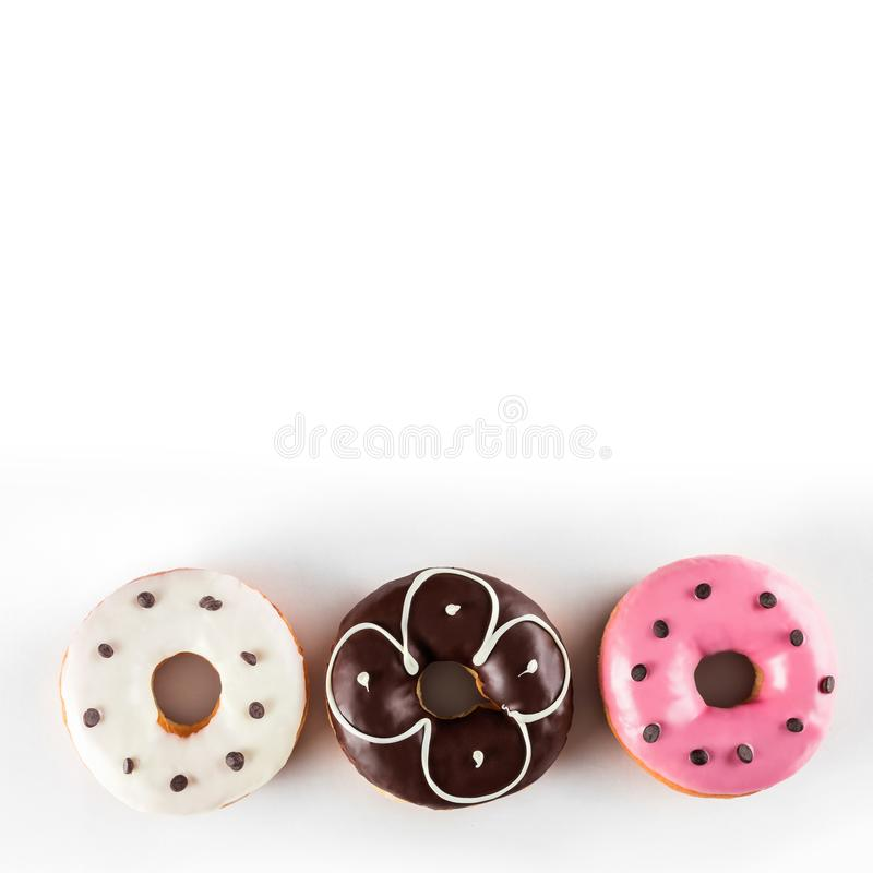 Assorted donuts with chocolate frosted and pink glazed isolated on white background, top view royalty free stock photos