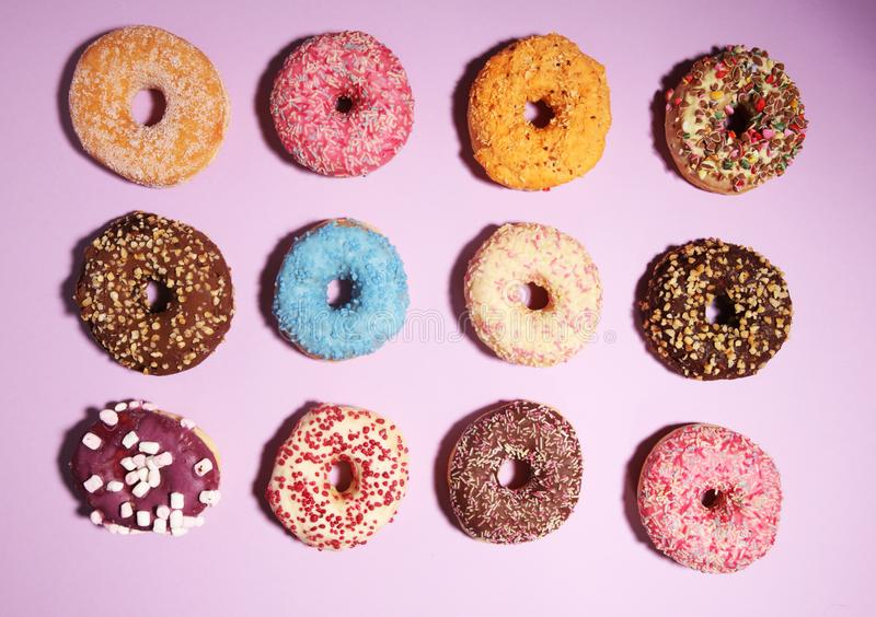 Assorted donuts with chocolate frosted, pink glazed and sprinkles donuts stock image