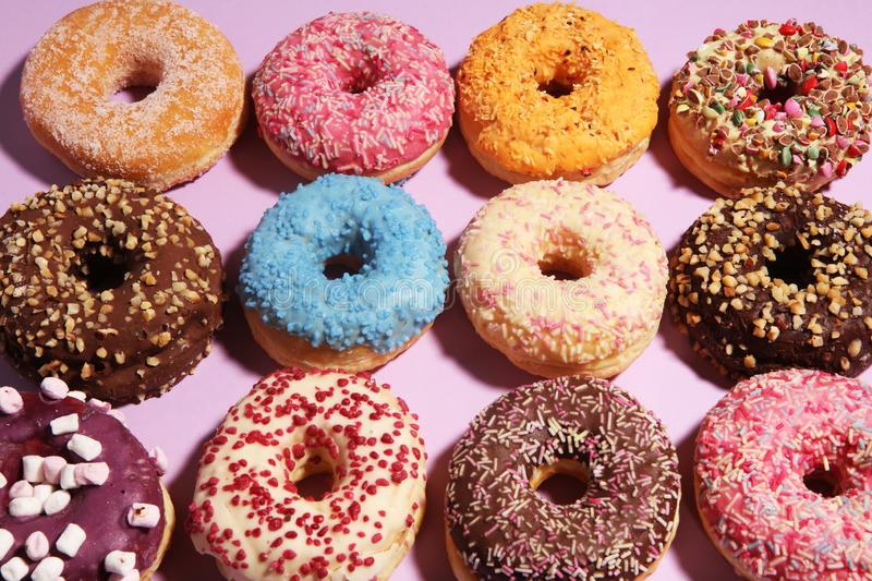Assorted donuts with chocolate frosted, pink glazed and sprinkles donuts royalty free stock photography