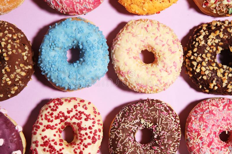 Assorted donuts with chocolate frosted, pink glazed and sprinkles donuts stock photography
