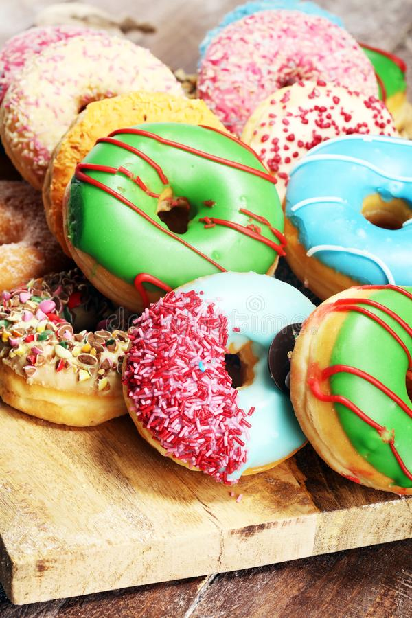 Assorted donuts with chocolate frosted, pink glazed and sprinkles donuts. on table stock images
