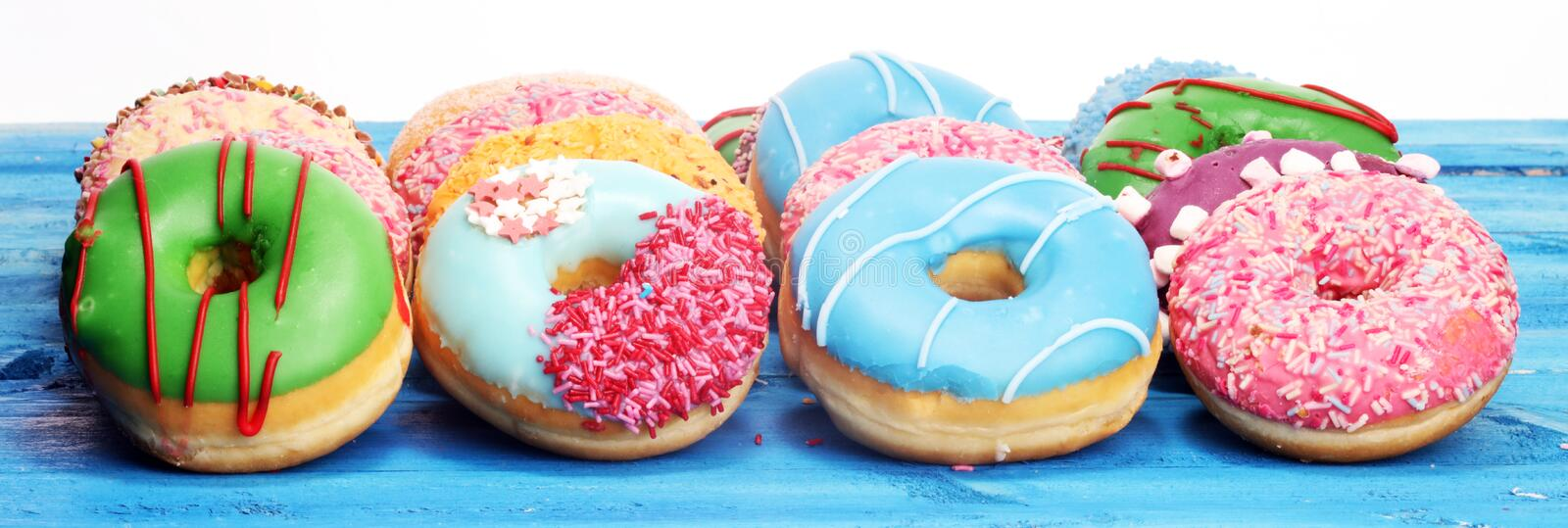 Assorted donuts with chocolate frosted, pink glazed and sprinkles donuts. on table royalty free stock photo