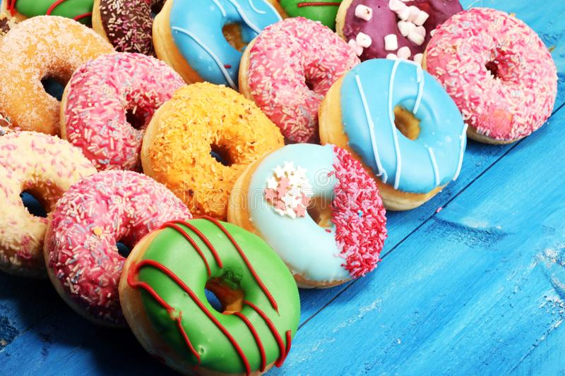 Donuts in different glazes with chocolate. Assorted donuts with chocolate frosted, pink glazed and sprinkles donuts royalty free stock image