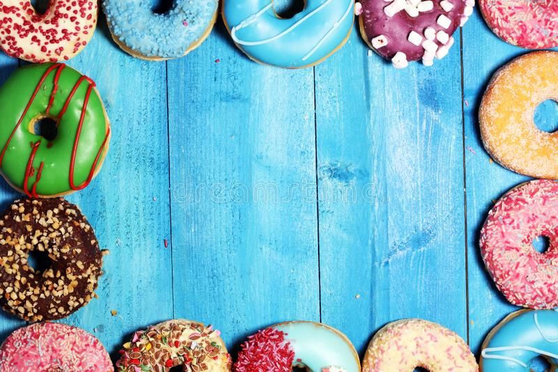 Donuts in different glazes with chocolate. Assorted donuts with chocolate frosted, pink glazed and sprinkles donuts stock image