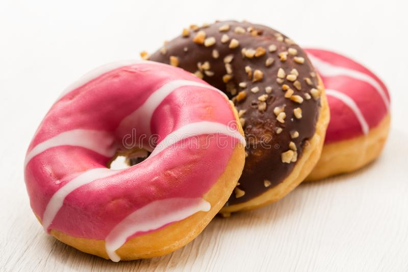 Assorted donuts with chocolate on white wood background stock photo