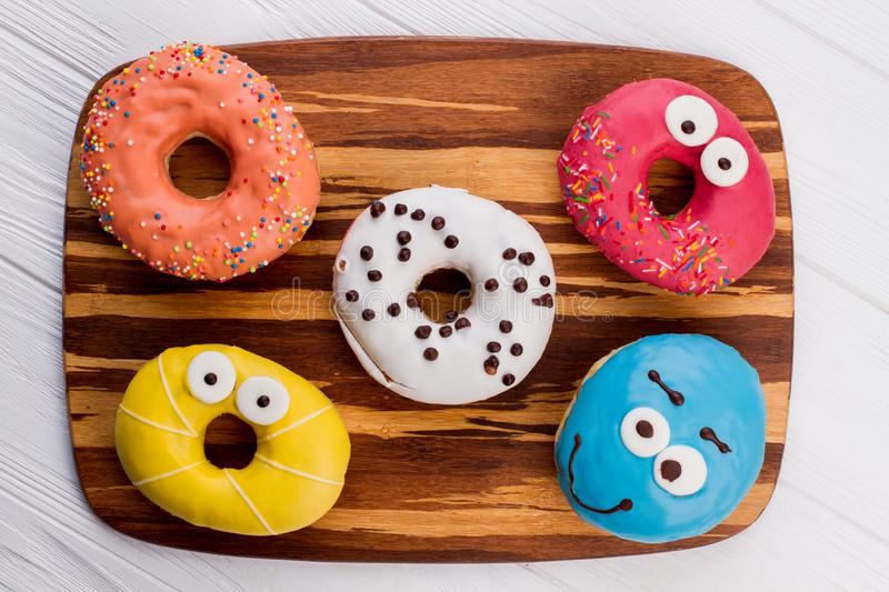 Assorted donuts on cutting board. Donuts of different flavors for breakfast stock images
