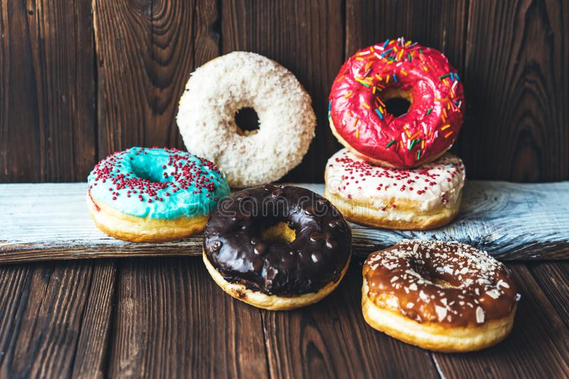 Assorted donuts on a dark wooden background. Assorted glazed appetizing donuts on a dark wooden background stock image