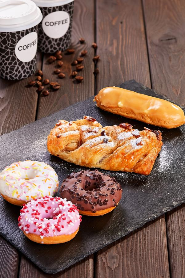 Assorted donuts with pink glazed, chocolate frosted and sprinkles stock image